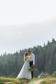 Sesión de fotos de una pareja de enamorados en las montañas. la niña está vestida como una novia con un vestido de novia.