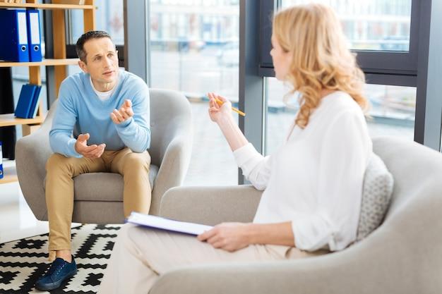 Sesión psicológica. hombre guapo agradable agradable mirando a su psicólogo y hablando con ella mientras habla de su problema