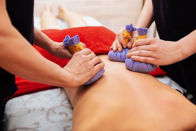 Durante la sesión de relajación. cliente en forma con una piel impecable que le masajea la espalda con bolsas especiales de hierbas azules