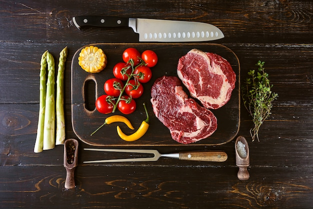 Set para cocinar una cena festiva para dos. dos filetes de carne marmoleada cruda, especias, verduras