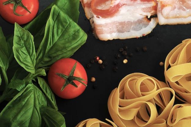 Set para cocinar pasta con nidos de pasta, tocino, hojas de albahaca y tomate.