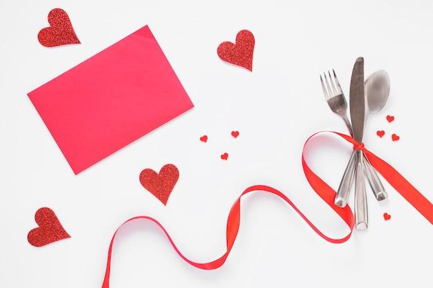 Set de cubiertos con corazones y papel rosa.