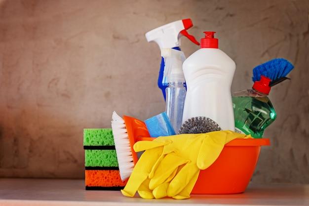 Set de limpieza con productos y suministros en mesa de cocina.