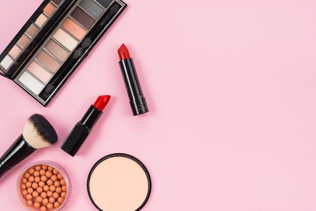 Set de maquillaje y complementos cosméticos sobre fondo rosa.