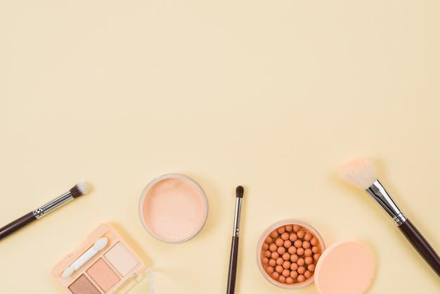 Set de maquillaje y productos cosméticos sobre fondo claro.