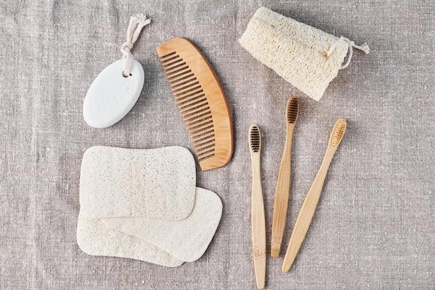Set natural para bañar cepillos de bambú, esponja luffa y cepillo de madera sobre fondo de lino. cero desperdicio sin concepto de plástico