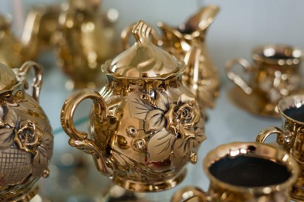 Set de oro para café y té con rosas dimensionales en las tazas.