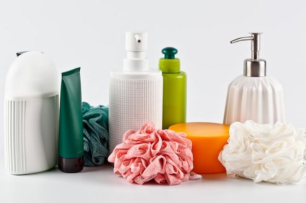 Set de productos cosméticos de baño y esponjas sobre superficie clara.