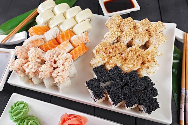Set de rollos de sushi servido en pizarra sobre fondo oscuro
