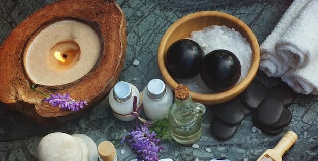Set para spa con aceite de masaje junto con velas y toallas blancas