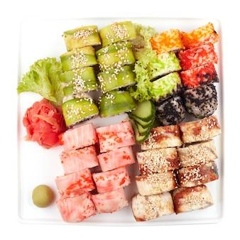 Set de sushi para una gran empresa, rollos, california, philadelphia con salsa de lava, jengibre y wasabi, fondo blanco aislado, vista desde arriba