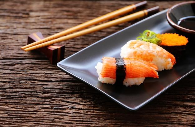 Set de sushi en plato cerámico estilo comida oriental japonesa.