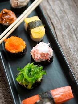 Set de sushi y rollos de sushi servidos en mesa de madera.