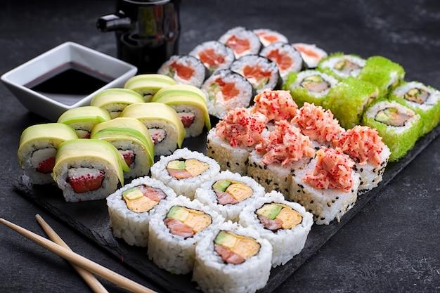 Set de sushi, sobre fondo negro, cinco tipos de rollos