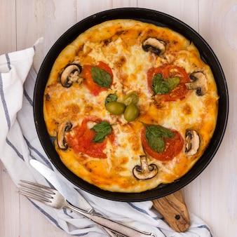 Seta; los tomates ingredientes de albahaca y aceitunas en pizza de queso con un tenedor sobre la mesa