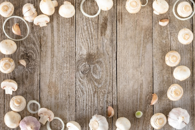 Setas de ajo y aros de cebolla en la mesa de madera vieja. vista superior