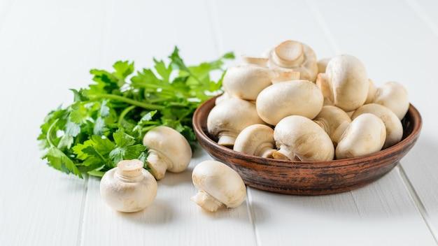 Las setas frescas en un cuenco de la arcilla con perejil se van en una tabla de madera blanca. cocina vegetariana.