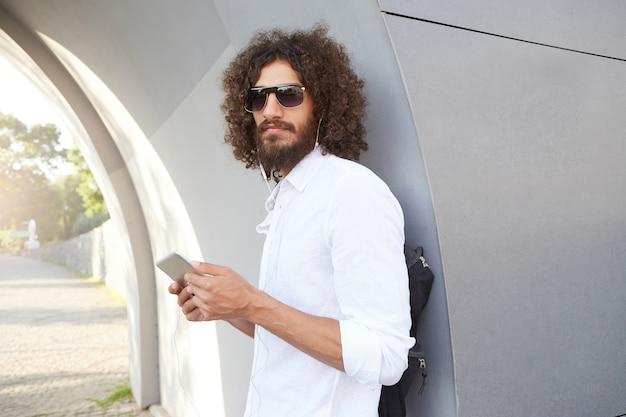 Severo apuesto joven con cabello rizado y barba posando en un día cálido y soleado, mirando seriamente con tableta en manos