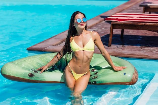 Sexual, feliz bastante joven vistiendo traje de baño de pie en la piscina, sosteniendo kiwi colchón inflable.