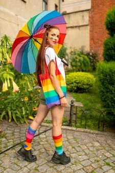 Sexy babe en ropa colorida y bandera lgbt en ella posando al aire libre.