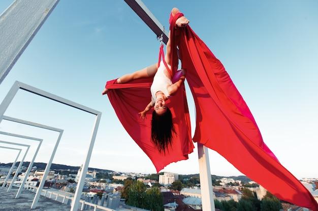 Sexy bailarina realizando danza aérea en el techo al atardecer