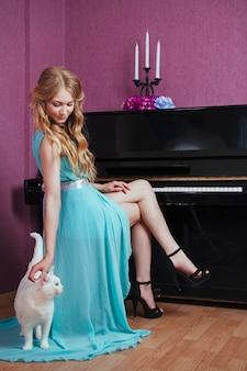Sexy hermosa chica rubia en vestido tocando el piano con un gato