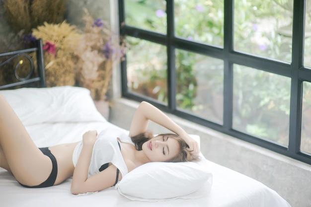 Sexy hermosa mujer morena acostada en la cama en sensual lencería negra
