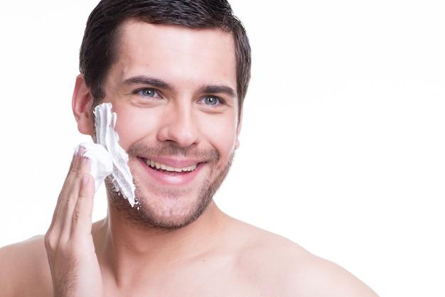 Sexy joven guapo con espuma de afeitar