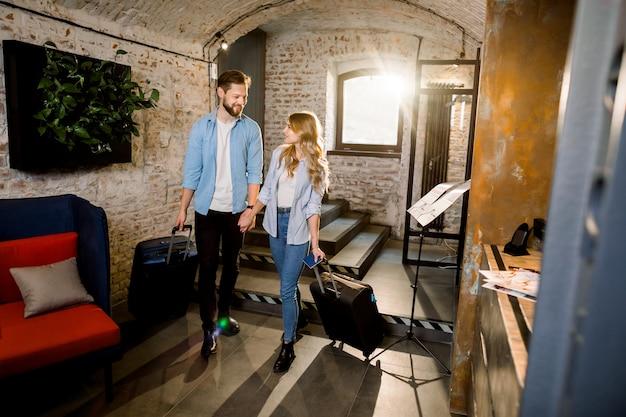 Sexy joven pareja amorosa entrando en el vestíbulo, tomados de la mano, tirando de sus maletas, concepto de personas que viajan por negocios
