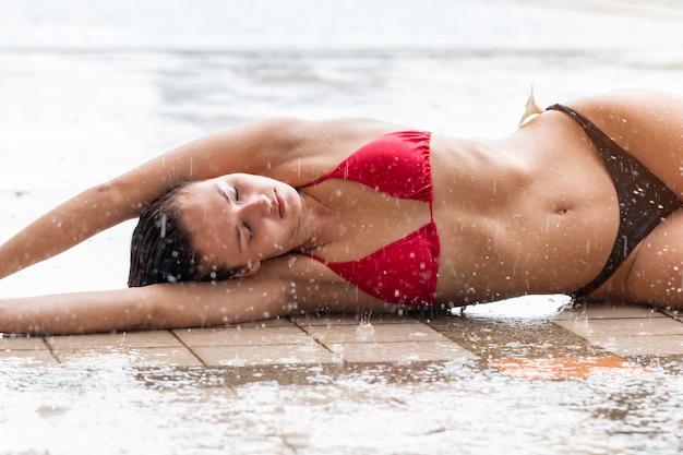 Sexy modelo de mujer atractiva caucásica usar bikini bajo la lluvia.