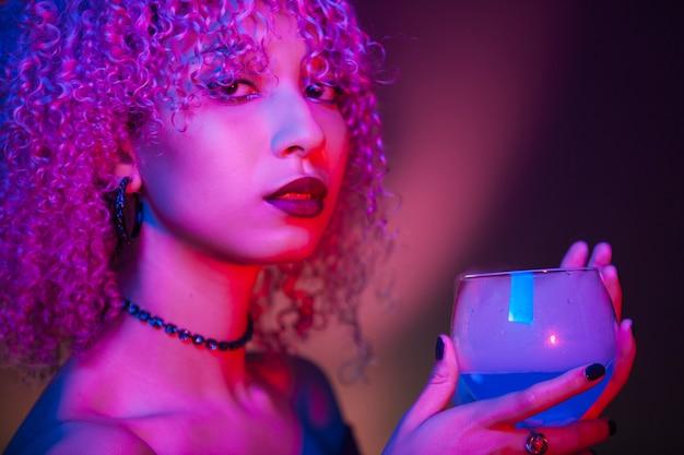 Sexy mujer afroamericana sosteniendo una bebida espirituosa azul