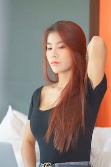 Sexy mujer asiática en bikini negro acostado en la cama