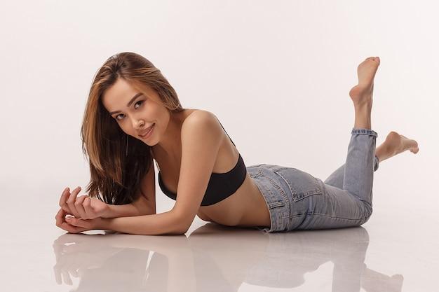 Sexy mujer asiática posando en lencería negra, jeans azul sobre fondo blanco de estudio