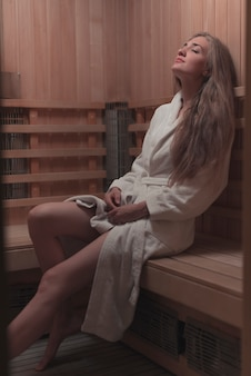 Sexy mujer joven relajante en sauna de madera
