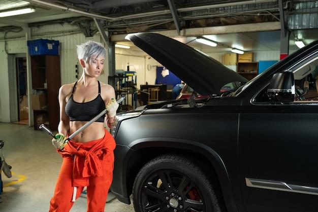 Sexy mujer joven reparando el automóvil en un servicio de automóviles