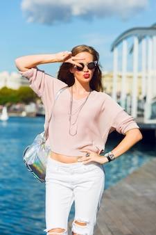 Sexy mujer joven en ropa blanca posando en el jardín junto al mar. foto de verano de moda. colores brillantes, gafas de sol