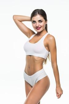 Sexy mujer joven en ropa interior blanca en la pared blanca, aislada
