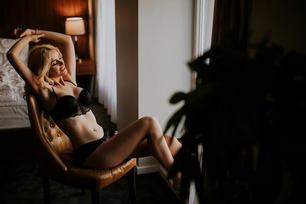 Sexy mujer joven en ropa interior posando en la habitación junto a la ventana