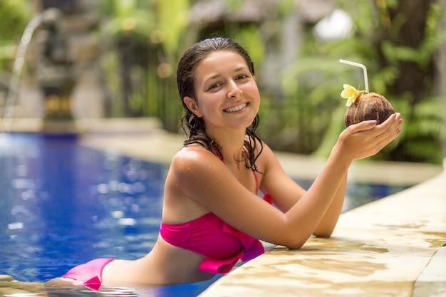 Sexy mujer joven en traje de baño rosa con bebida de coco en la piscina de vacaciones