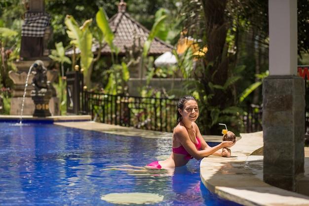 Sexy mujer joven en traje de baño rosa con bebida de coco en la piscina de vacaciones.