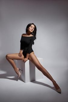 Sexy mujer morena con cabello largo, cuerpo delgado de figura perfecta. maquillaje natural en una carita de niña