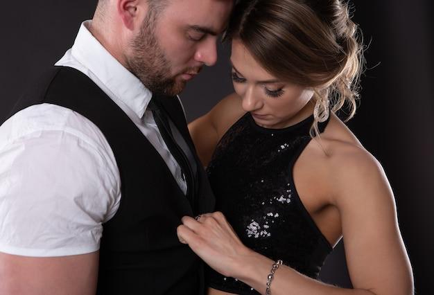 Sexy mujer rubia en un ataque de pasión desabotona su ropa en su hombre