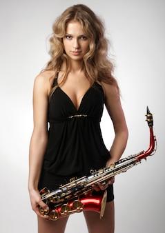 Sexy mujer rubia atractiva con saxofón