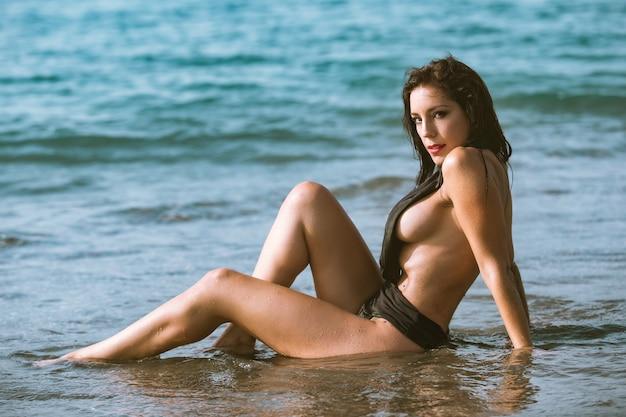 Sexy, mujer se sentar, en la playa, en, biquini