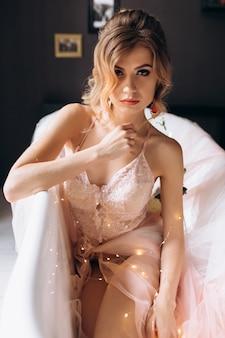 Sexy rubia joven en lencería reluciente se encuentra en el baño cubierto de seda