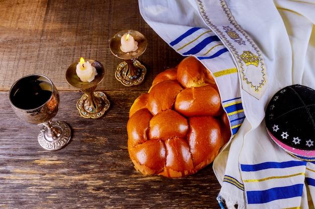 Shabat challah pan, vino shabat y velas en la mesa. vista superior