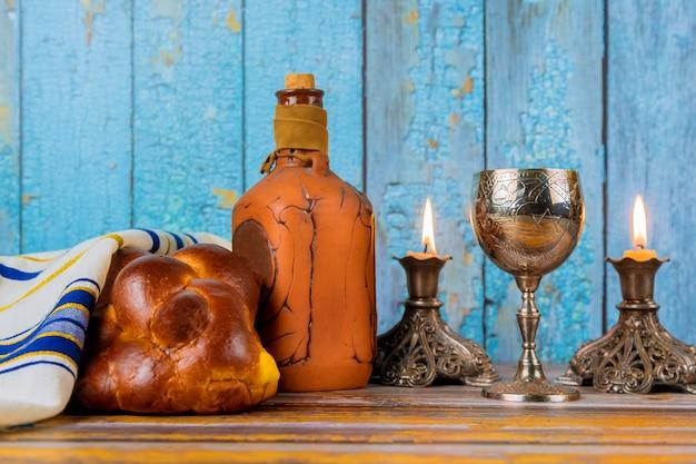 Shabat con jalá pan sobre una mesa de madera velas y copa de vino.