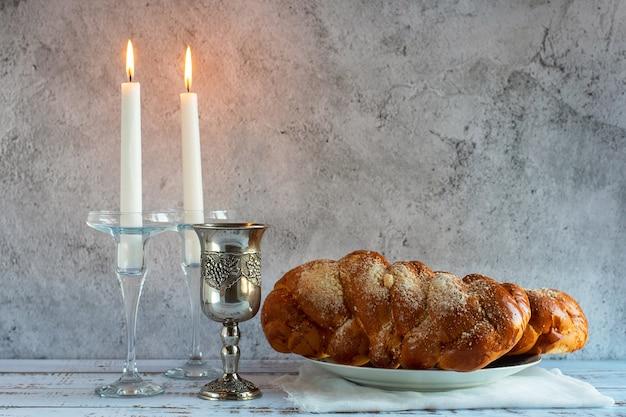 Shabat shalom - pan jalá, vino de shabat y velas en la mesa de madera