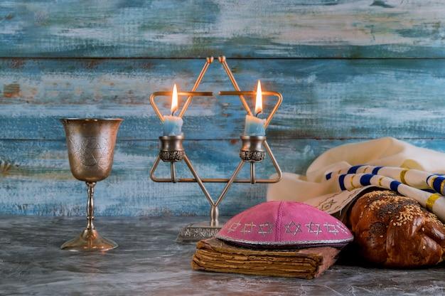 Shabat víspera velas de mesa y copa de vino con pan jalá cubierto,