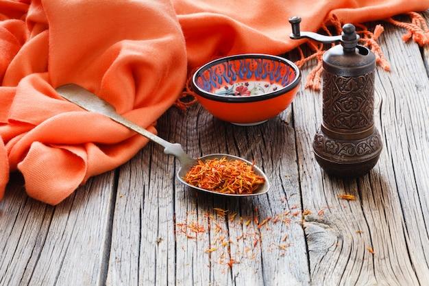 Shafran en una cuchara en la mesa de madera con tela de seda